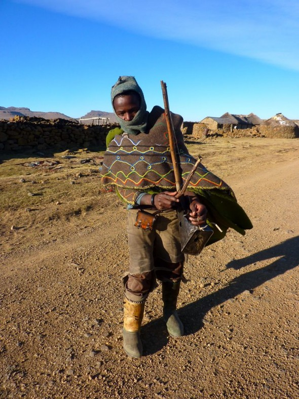 Boy playing string instrument improvised from scrap, Lesotho.