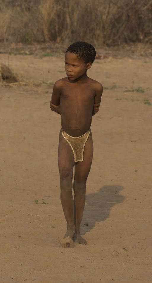 Young bushman girl standing. Ju/'hanse San people, or as they are more commonly known, the Bushmen, near Tsumkwe, eastern Namibia.