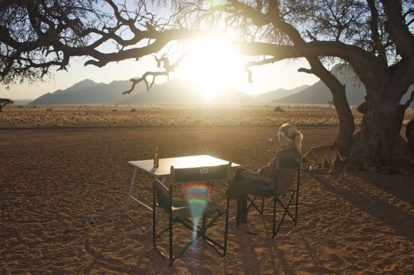 Lucie sitting at camping table watching the sunset in Namtib Reserve, Namibia.