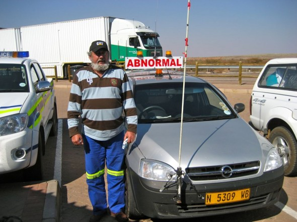Man standing next to car with Abnormal sign to signify a wide load ahead, Namibia.