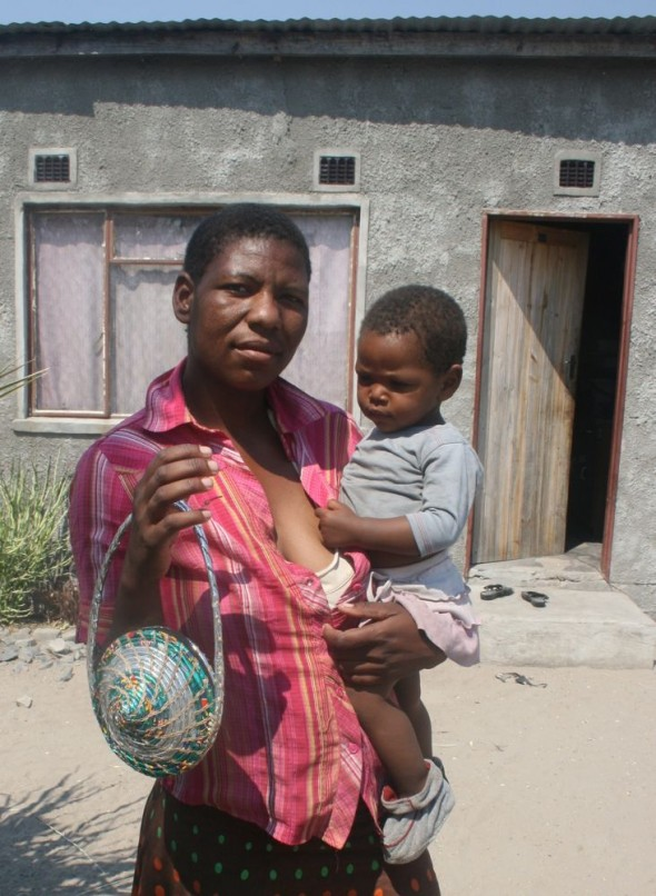 Penane holding her baby and a Vagabond Van Chip Bag, Maun, Botswana.
