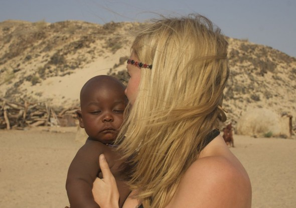 Lucie holding a Himba baby, Purros Himba tribe village, Namibia.