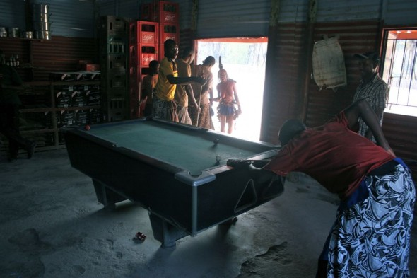 Himba guys playing pool in a local shabine (pub), Epupa Falls, Namibia.