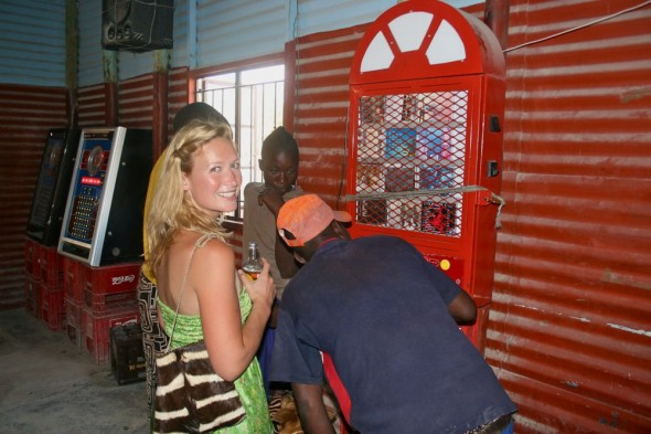 Lucie and friends selecting a song on the jukebox at a local shabine (pub) at Himba guys playing pool in a local shabine (pub), Epupa Falls, Namibia.