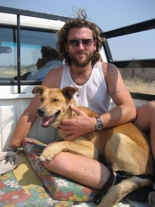 Bow Wow feeling safe and Lachlan in the back of a ute driving down dusty road. Grootfontein, Namibia.