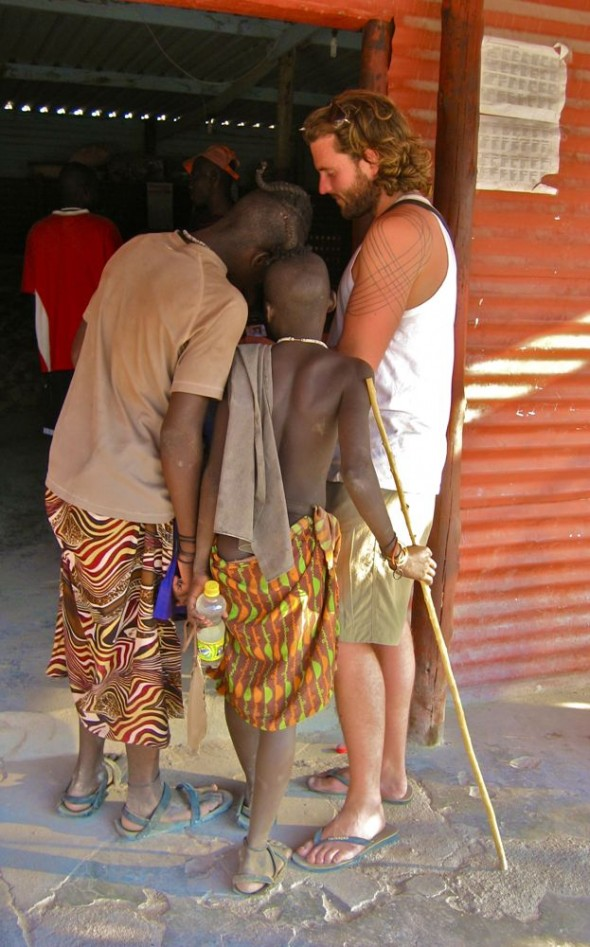Lachlan shows the Himba guys photos on his camera out the front of the local shabine (pub) / shop, Epupa Falls, Namibia.
