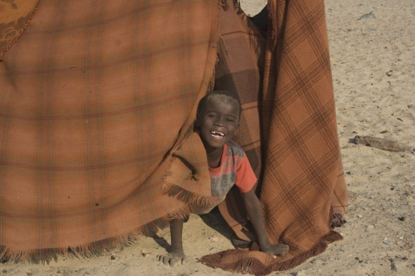 Himba boy hiding behind blanket in hut, Purros Himba tribe village, Namibia.