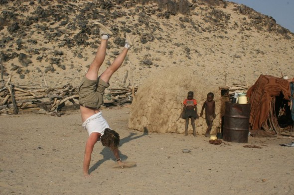 Lachlan walking on his hands at Purros Himba tribe village, Namibia.