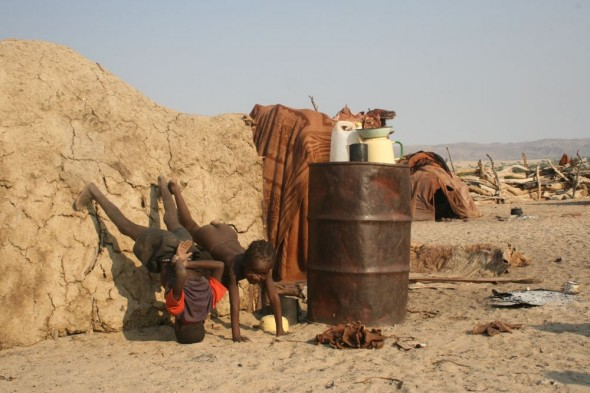 Himba children learning to do hand stands at Purros Himba tribe village, Namibia.