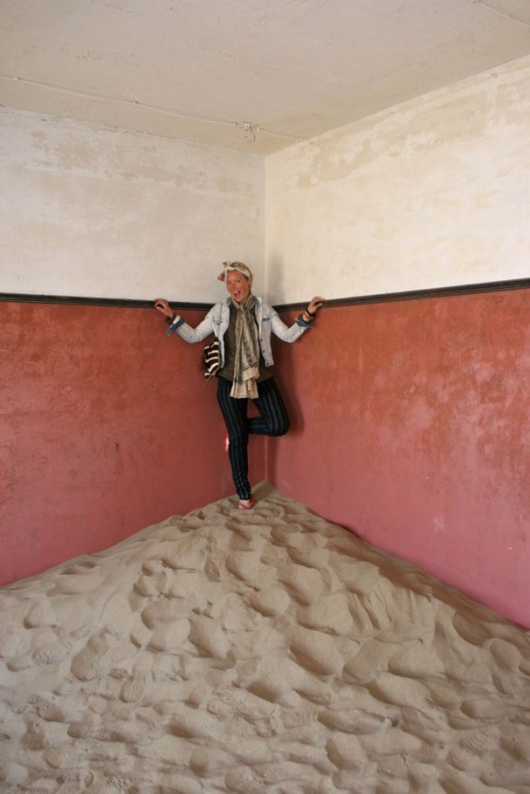 Lucie standing on a pile of sand inside an abandoned house in Kolmanskop diamond mining ghost town, Namibia.