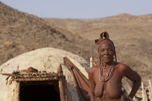 Himba elder / grandmother outside her hut at Purros Himba tribe village, Namibia.