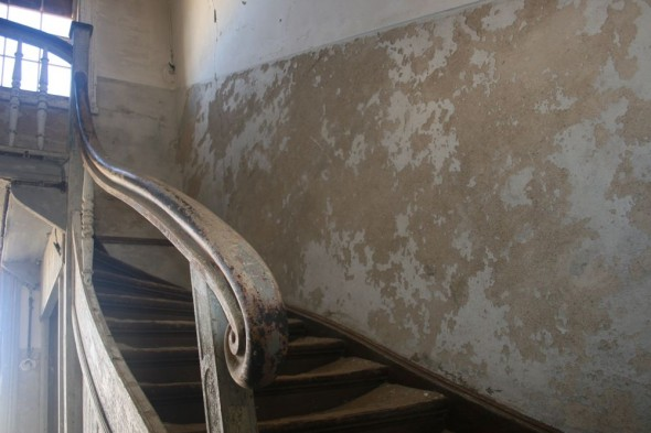 An antique staircase in abandoned house in Kolmanskop diamond mining ghost town, Namibia.