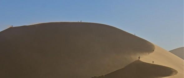 People walking up the Sossusvlei sand dunes, Namibia.