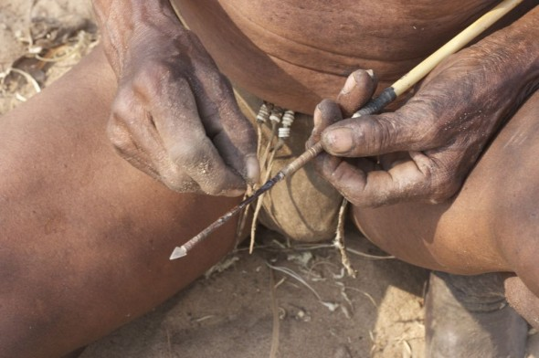 Bushman making a sharp arrow. Ju/'hanse San people, or as they are more commonly known, the Bushmen, near Tsumkwe, eastern Namibia.