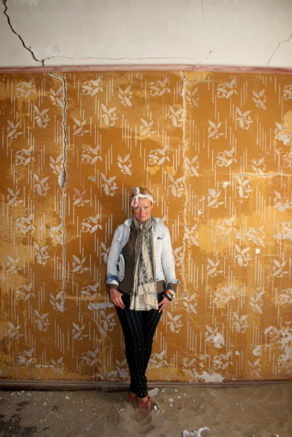 Lucie posing in front of antique wallpaper in Kolmanskop diamond mining ghost town, Namibia.