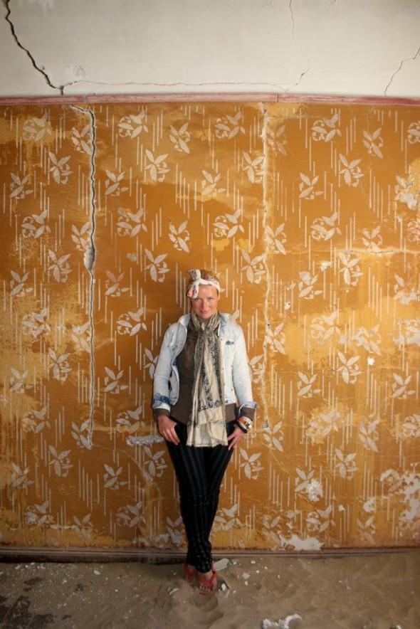 Lucie posing in front of antique wallpaper in Kolmanskop diamond mining ghost town, Namibia.