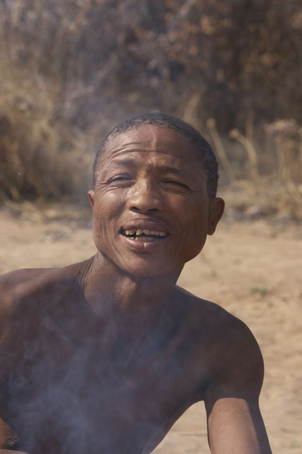 Bushman making a fire with smoke in his face. Ju/'hanse San people, or as they are more commonly known, the Bushmen, near Tsumkwe, eastern Namibia.