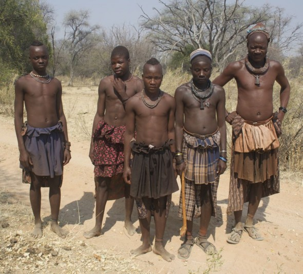 A group of Himba men with their tiered skirts and jewellery, Kaokoland, Namibia.