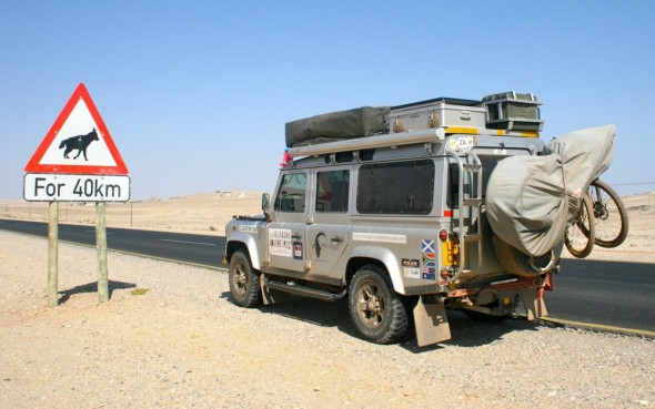 Lula the Landy parked besided Brown Hyena warning sign on Namibian highway, Lüderitz, Namibia.