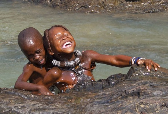 Himba children playing in the Kunene river, Epupa Falls, Namibia.