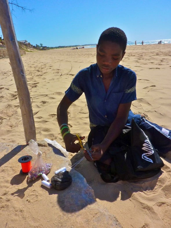 Entrepreneurial young boys make trinkets for tourists with shells that they collect along the shore. Impressed with their skill and ingenuity, we commissioned some lovely headbands for Vagabond Van. Praia do Tofo, Mozambique.