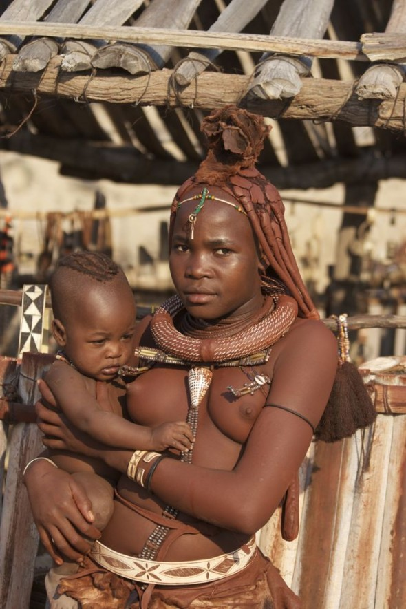 Himba woman and baby with jewellery, Purros Himba tribe village, Namibia.