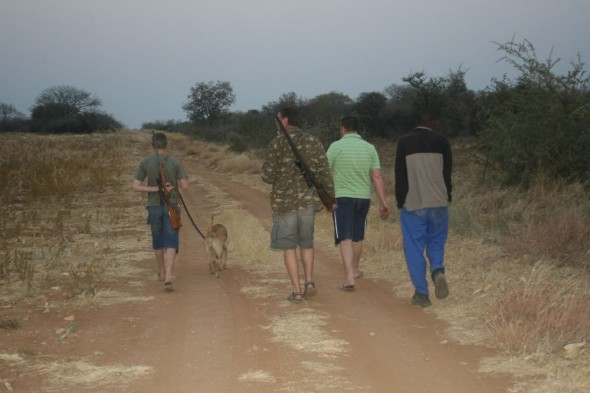 Eugene's family walking down dirt road in search of warthog for hunting. Grootfontein, Namibia.
