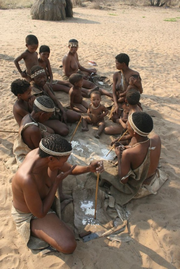 Group of women making jewellery with baby in the middle. Ju/'hanse San people, or as they are more commonly known, the Bushmen, near Tsumkwe, eastern Namibia.