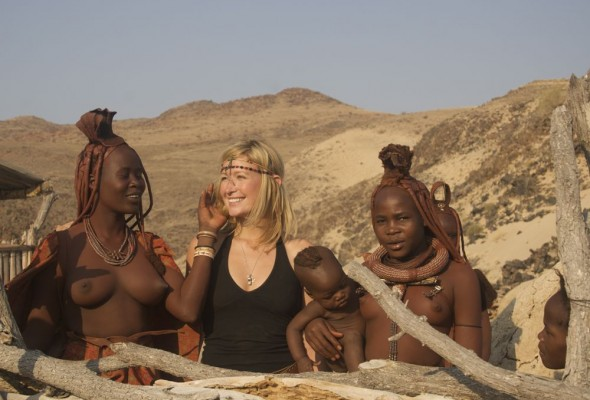 Himba women intrigued by Lucie's blonde hair at Purros Himba tribe village, Namibia.