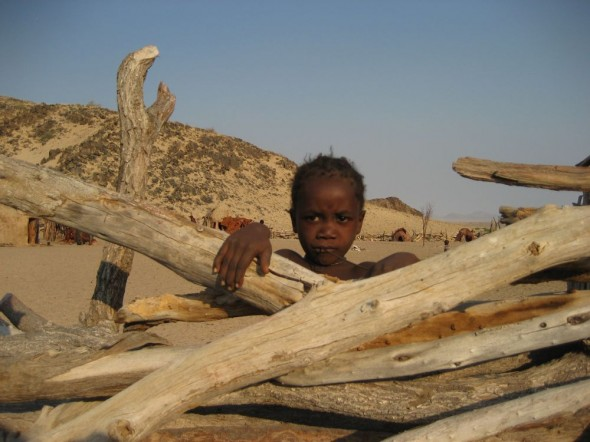 Himba girl in front of fence at Purros Himba tribe village, Namibia.
