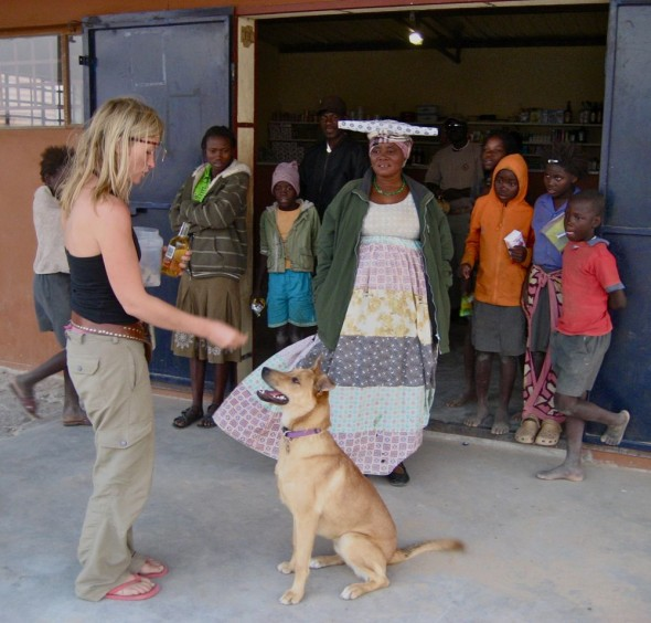 Lucie getting Bow Wow to do tricks in front of local people and Herero woman at Purros, Namibia.