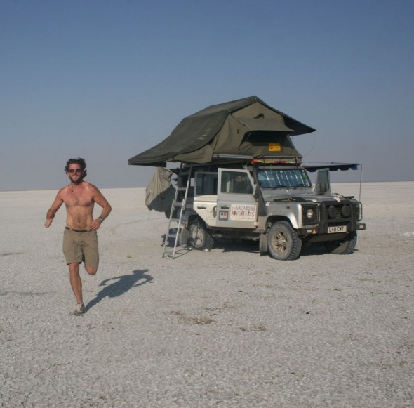 Lachlan from The Vagabond Adventures running with Lula the Landy in the background. The Makgadikgadi Pan, Botswana.
