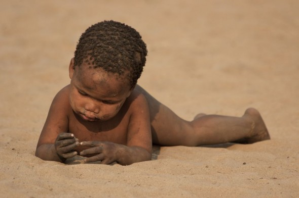 Baby lying in the sand covered in dirt. Ju/'hanse San people, or as they are more commonly known, the Bushmen, near Tsumkwe, eastern Namibia.