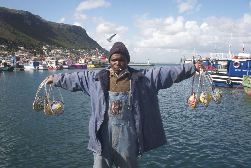 Fisherman holding the Chip Bags in Kalk Bay, Cape Town, South Africa.
