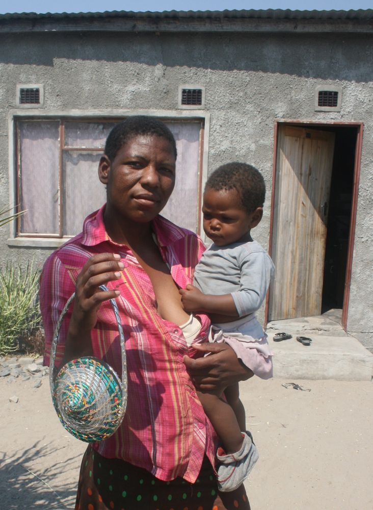 Penane and her baby holding a Vagabond Van Chip Bag, Maun, Botswana, Africa.