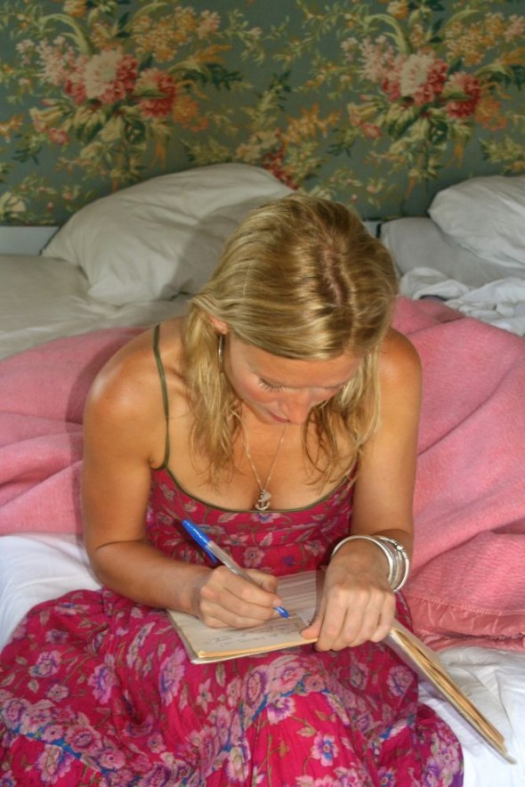 Lucie writing in guest comments book at Great Zimbabwe Ruins in rondavel.