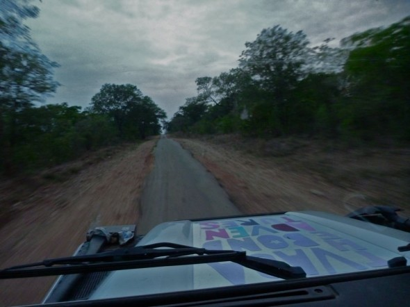 Lula the Landy driving on a single track road heading for Great Zimbabwe Ruins and chasing the sunset.