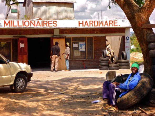 Millionaires Hardware with colourful guy sitting on tyre out front, Rusape, Zimbabwe