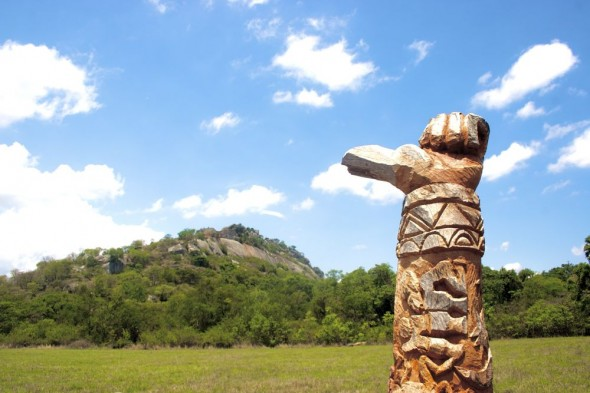 Wood carving pointing at the Great Zimbabwe Ruins.