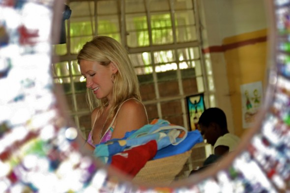 Lucie in the mirror adorned with rolled varnished paper looking at jewellery, Harare, Zimbabwe