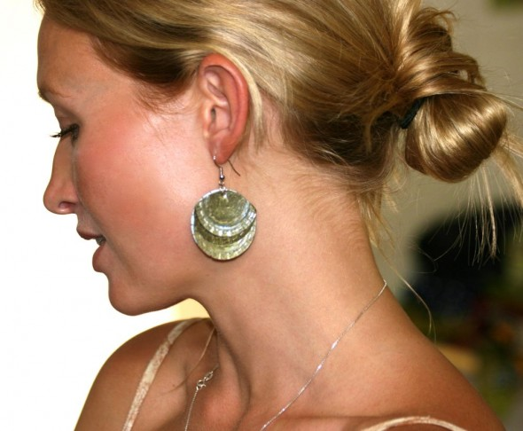 Lucie wearing earrings made from bottle caps, Harare, Zimbabwe
