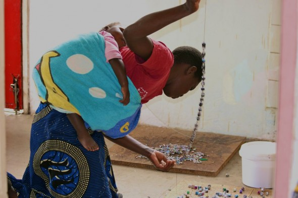 Woman with baby on her back making jewellery, Harare, Zimbabwe
