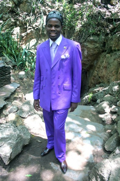 Man wearing a purple suit standing at the entrance to the Chinhoyi Caves, Zimbabwe