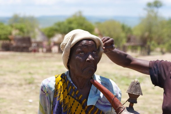 Lifting old woman's hat so that we can see her face in the sun, near Binga, Zimababwe