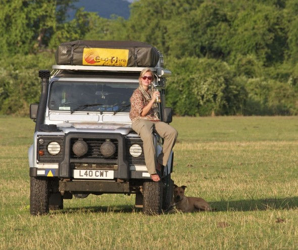 Lucie girl sitting on Lula Land Rover drinking Savana Dry at Lake Kariba, Zimbabwe