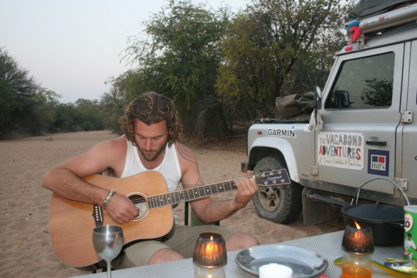 Lachlan playing guitar, camping on dry river bed, Kaokaland, Namibia