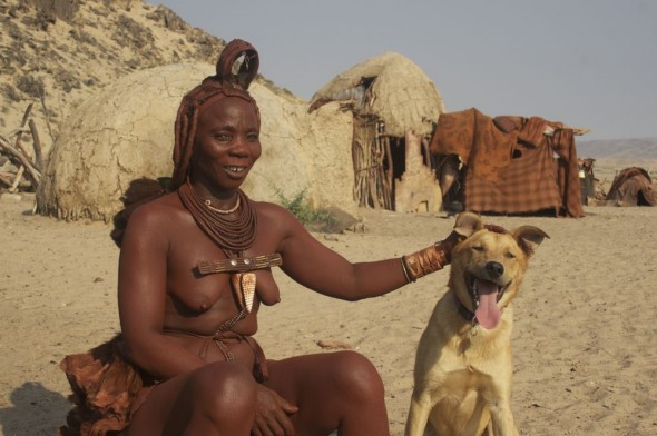 Himba woman with Bow Wow, Purros Himba tribe village, Namibia.