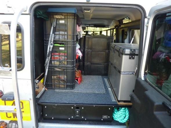 Rear inside view of Land Rover Defender 110 with fridge and pull out drawer