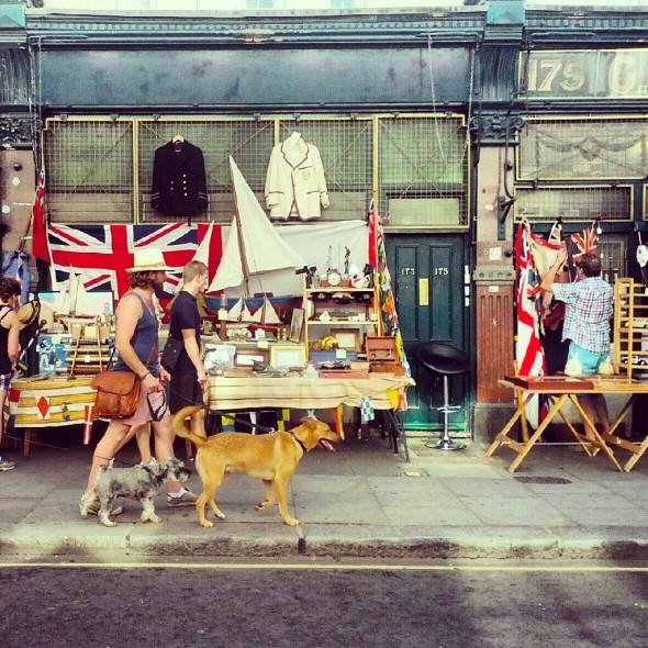 Bow Wow and Lachlan walking down Portobello road with british flags and market stall