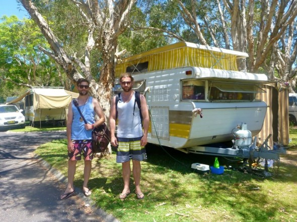 Hamish and Lachlan at the caravan park in Byrons Bay in New South Wales in Australia in the sunshine by a retro caravan ready to go exploring.